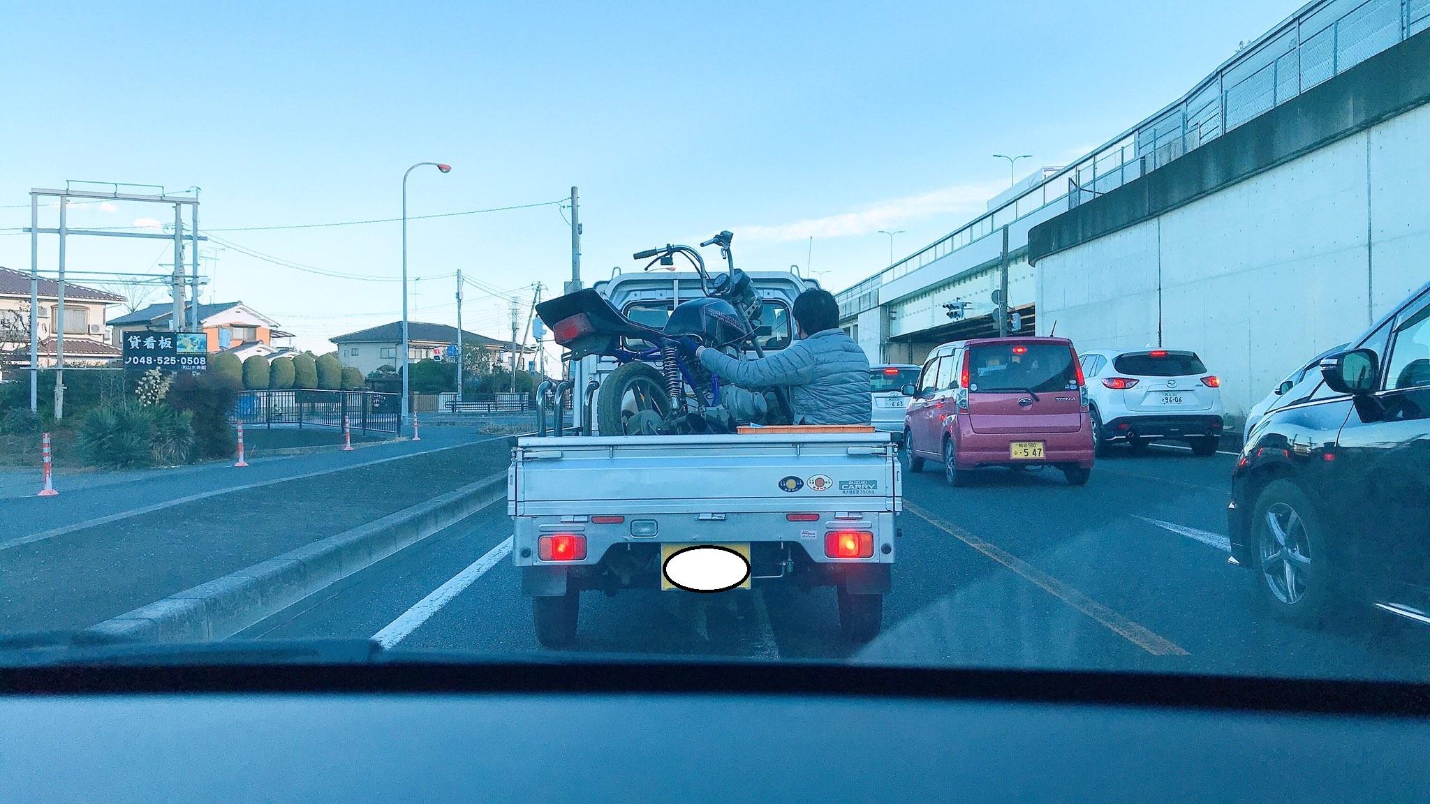 軽トラの荷台で荷物を支える人